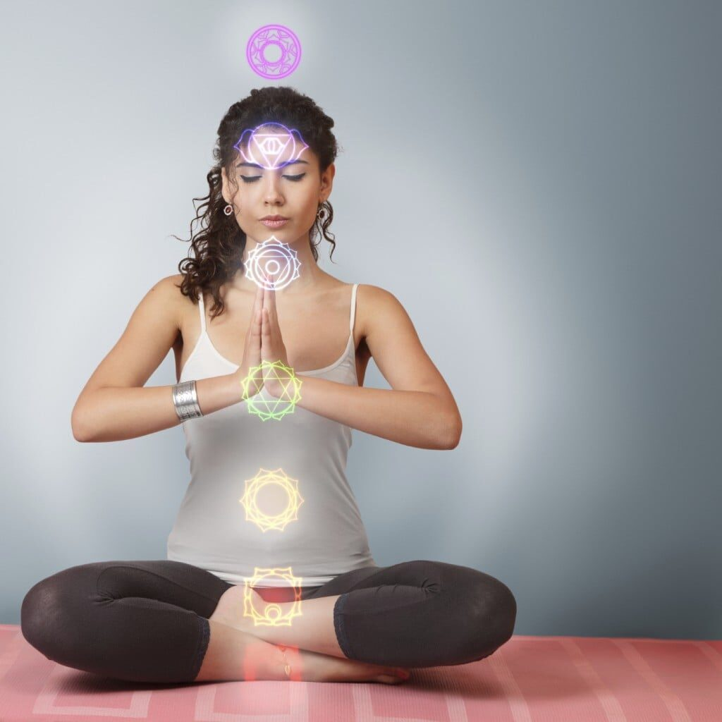 Beautiful young woman doing yoga meditation in lotus position with activated chakras over body